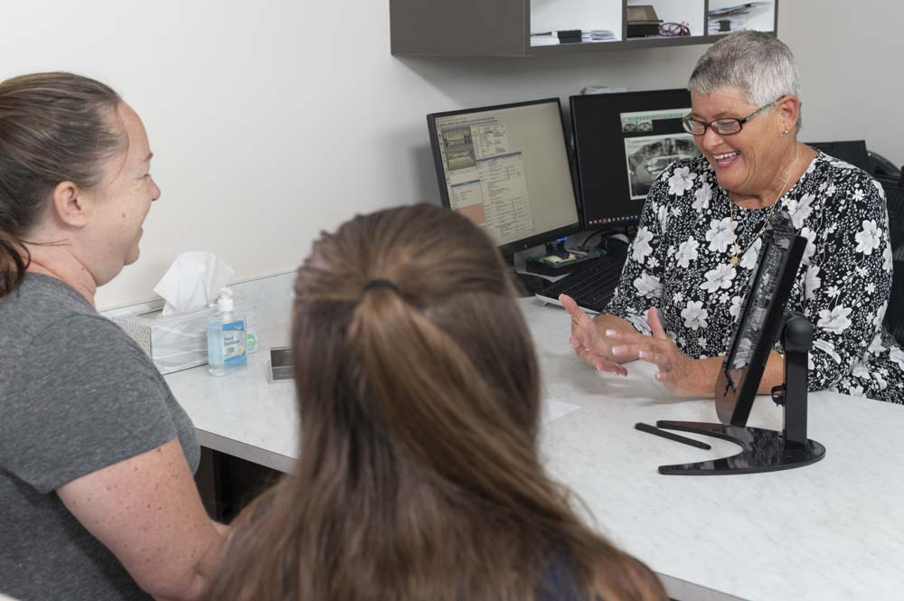 The office manager at Moorehead Family Dentistry speaks to dental patients during a consultation